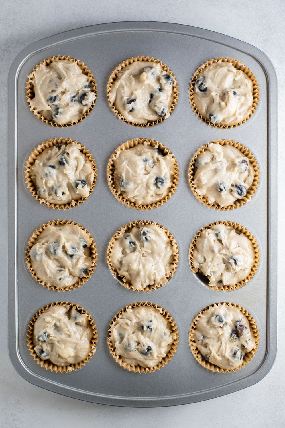 Blueberry muffin batter in cups in a muffin tin.